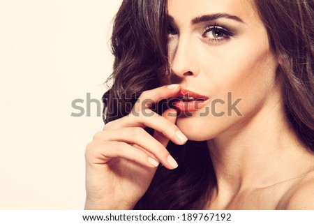 beauty portrait of young woman touch her lips studio shot