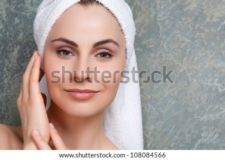 Beauty portrait of young woman with towel on head at spa - stock photo