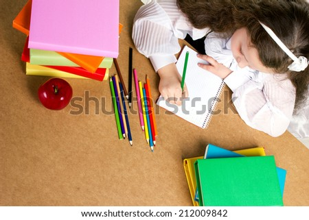 beauty preschooler girl  in white and black uniform diligently writing in copybook, near -  red apple, many colorful books and pencils, top view - stock photo