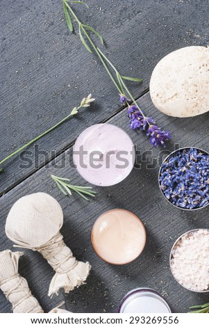 beauty product samples with fresh purple and blue dried lavenders, bath salts and massage pouches on dark wood table background
