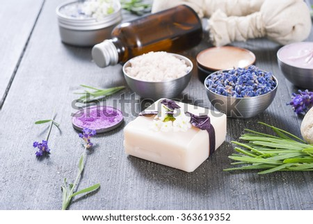 beauty product samples with fresh purple and blue dried lavenders, bath salts and massage pouches on dark wood table background - stock photo