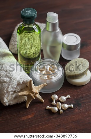 Beauty products. Cosmetics for face and body - toner, lotion, cream, capsules with rejuvenating facial oil, handmade soap,towel. On dark wooden surface - stock photo
