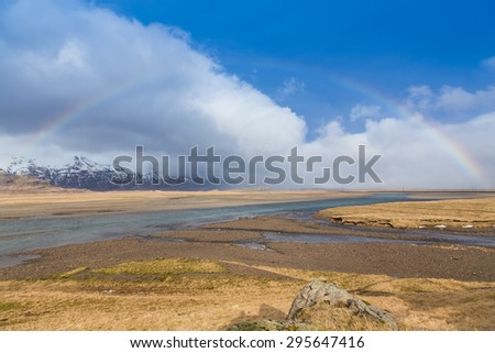 Beauty rainbow of wheat field in late winter with beauty of blur sky, Iceland - stock photo