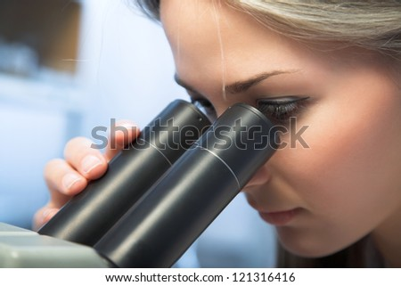 beauty researcher looking through microscope in laboratory - stock photo