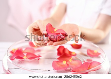 Beauty ritual for hands. Care treatment of hands and nails woman hands over the bowl with rose petals  - stock photo