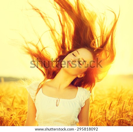 Beauty Romantic Girl Outdoors. Beautiful Teenage Model girl Dressed in Casual Short Dress on the Field in Sun Light. Blowing Long Hair. Autumn. Glow Sun, Sunshine. Backlit - stock photo