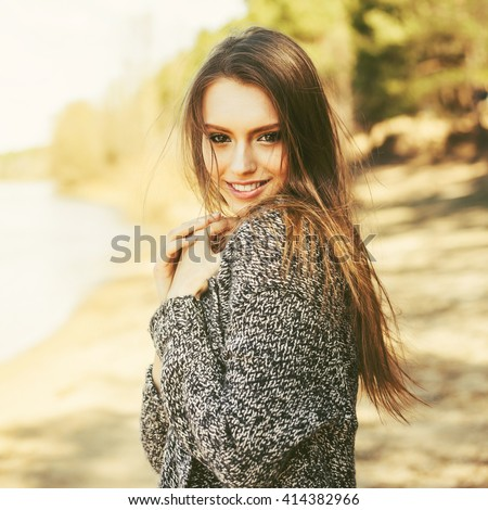 Beauty Romantic Girl Outdoors. Beautiful Teenage Model l Dressed in sweater on the bank of the river in Sun Light. Blowing Long Hair. Autumn. Glow Sun, Sunshine. Backlit. Toned in warm colors - stock photo