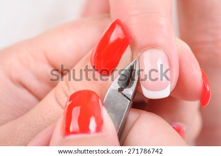 beauty salon, manicure applying, cutting the cuticle with special cutter - stock photo