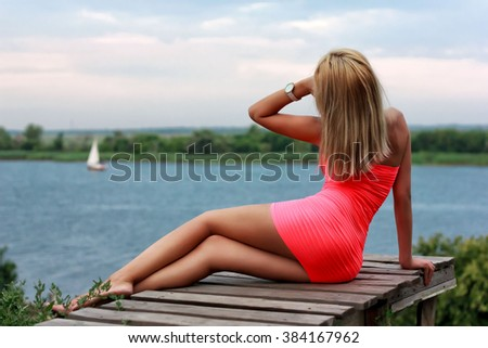 Beauty sexy girl on the wooden jetty looking to the sailing yacht in the river - stock photo