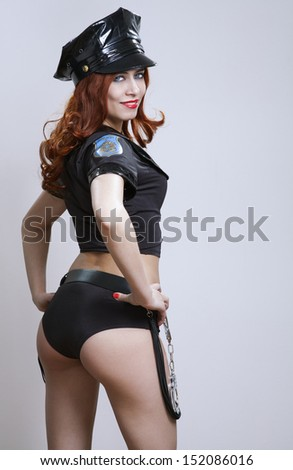 beauty sexy police woman on gray background - stock photo