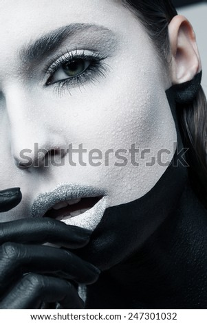 Beauty shot of a woman with geometrical makeup and long eyelashes - stock photo