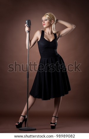 Beauty singer - woman pin-up portrait in black with microphone