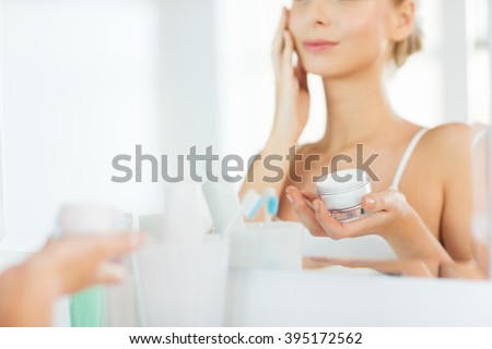 beauty, skin care and people concept - close up of smiling young woman applying cream to face mirror reflection at home bathroom - stock photo