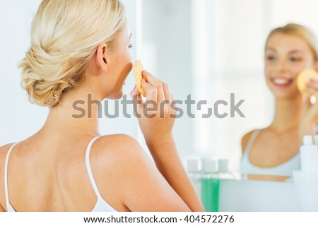 beauty, skin care and people concept - close up of smiling young woman washing her face with facial cleansing sponge at home bathroom - stock photo