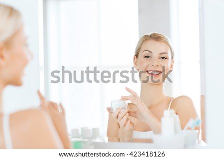beauty, skin care and people concept - smiling young woman applying cream to face and looking to mirror at home bathroom - stock photo