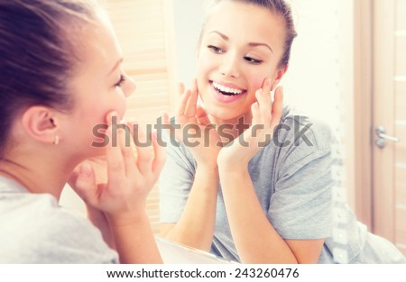 Beauty skin care. Young beautiful teenage girl touching her face before the mirror, enjoying her clean skin. Pretty woman touching her cheek and smiling. Perfect pure skin. Fresh Clean Skin. Skincare