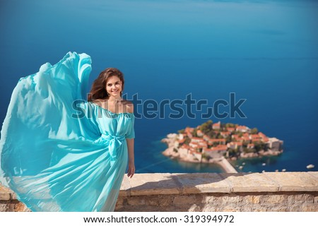 Beauty smiling brunette Girl in blowing dress Outdoors. Happy Young Woman Enjoying Nature. Beautiful Young model having Fun over sea and blue sky. Sveti Stefan, Montenegro.   - stock photo