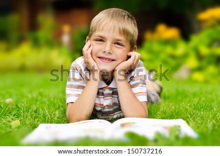 Beauty smiling child boy reading book outdoor on green grass field  - stock photo