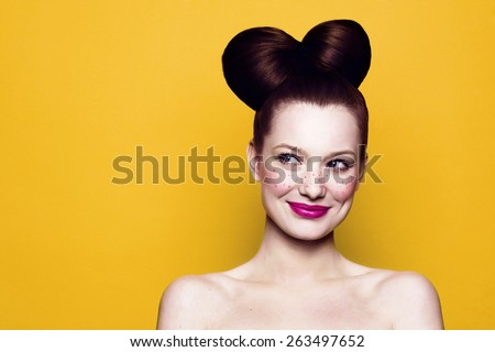 Beauty Smiling Teenager Model Girl. Beautiful Joyful teen girl with freckles, funny hairstyle and bright makeup. Isolated on a yellow background - stock photo