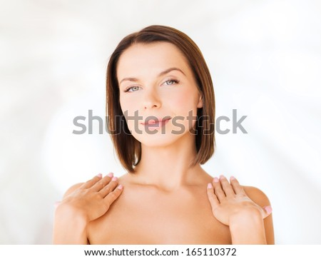 beauty, spa, health and people concept - beautiful woman touching her shoulders