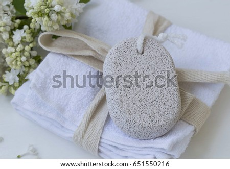Beauty spa with body care pumice stone on white towels with lilac flowers, bath spa products