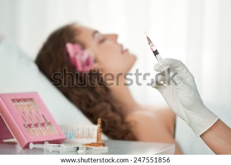 Beauty Spa: Young Beautiful Woman Having Cosmetic Injection of Botox . Selective Focus is on the Hand with Syringe - stock photo