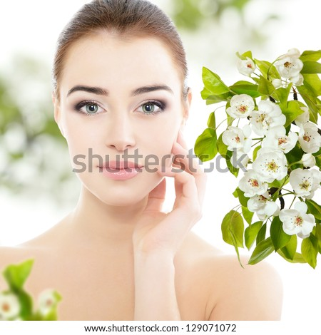 beauty spring girl portrait over blooming tree with flowers, young beautiful woman with clean skin holding hand near face - stock photo