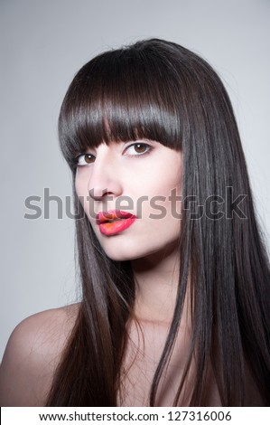 Beauty studio portrait of pretty brunette girl with healthy long straight hair, long fringe, clear skin, elegant makeup with slightly open glossy colorful red lips, naked shoulders, looking at camera - stock photo
