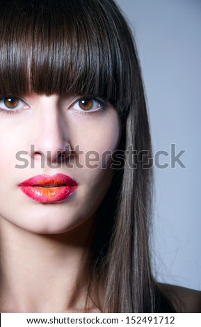 Beauty studio portrait of pretty brunette girl with healthy long straight hair, long fringe, clear skin, elegant makeup with slightly open glossy colorful red lips, naked shoulders, looking at camera