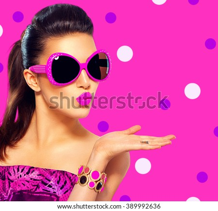 Beauty surprised fashion model girl wearing purple sunglasses, with bright makeup showing empty copy space on open hand palm for text over pink background. Emotions. Beautiful woman, summer fashion - stock photo