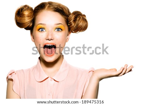 Beauty Surprised Teenager Model Girl. Beautiful Joyful teen girl with freckles, funny red hairstyle and yellow makeup. Open hand. Professional make up. Isolated on a white background - stock photo
