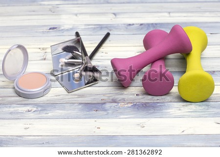Beauty tools: make-up and colorful weights - stock photo