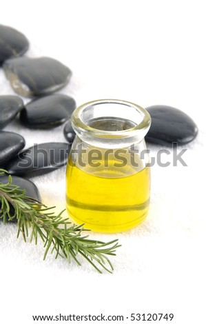 beauty treatment- bottle of aromatherapy oil and fresh green leaves - stock photo