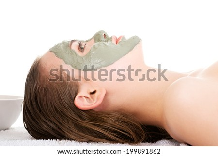 Beauty treatment in spa salon. Woman with facial clay mask. Isolated on white - stock photo