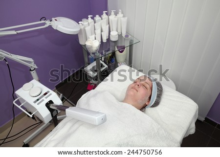 Beauty treatment of face skin with ozone facial steamer in SPA center - stock photo