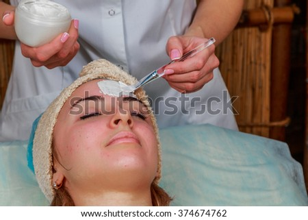 Beauty treatments for problem skin. The girl in the spa salon, applying cream. - stock photo