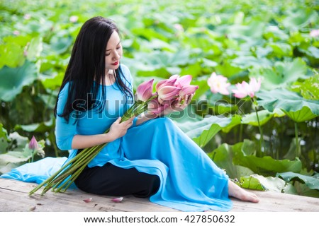 Beauty Vietnamese women wear traditional in lake of lotus.The Ao dai ( long-dress Vietnamese) is traditional costume of Vietnamese woman