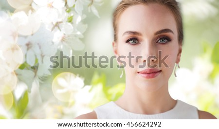 beauty, wedding and people concept - face of beautiful woman or bride in white dress over natural spring cherry blossom background - stock photo