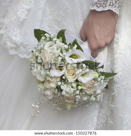 beauty wedding bouquet of yellow and cream roses in a bride hands.  - stock photo