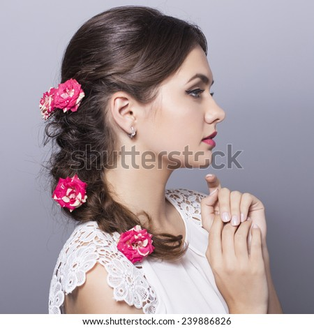 Beauty Wedding Bride Woman Portrait in a white dress and salon bridal make up and  hairstyle with red flowers. Neutral background - stock photo