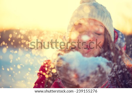 Beauty Winter Girl Blowing Snow in frosty winter Park. Outdoors. Flying Snowflakes. Sunny day. Backlit. Joyful Beauty young woman Having Fun in Winter Park. Defocused - stock photo