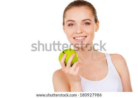 Beauty with green apple. Beautiful young woman holding a green apple and smiling while standing isolated on white - stock photo