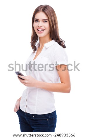 Beauty with mobile phone. Beautiful young women holding mobile phone and smiling while standing against white background - stock photo
