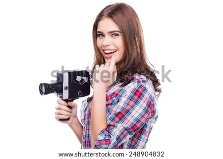 Beauty with movie camera. Cheerful young woman holding movie camera and smiling while standing against white background - stock photo