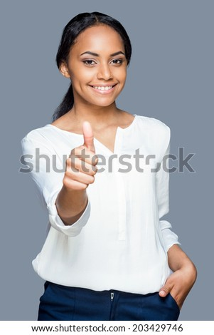 Beauty with thumb up. Waist up of attractive young African woman showing her thumb up and smiling while standing against grey background - stock photo