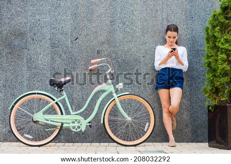 Beauty with vintage bike. Beautiful young smiling woman standing near her vintage bicycle on the street  - stock photo
