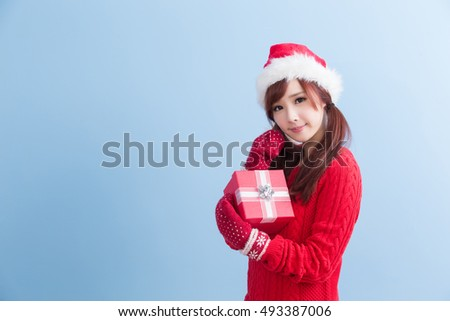beauty woamn take gift and smile to you in christmas isolated on blue background, asian