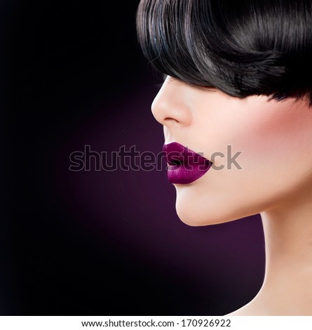 Beauty Woman Face close up with Beautiful Dark Violet Lips and Black Hair. Fringe Hairstyle. Perfect Skin. Trendy Matte Violet Lipstick. Model Face. Sensual Lips Closeup. Makeup.  - stock photo