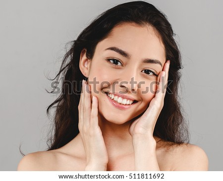 Beauty Woman Face. Portrait of a beautiful young woman with perfect skin closeup  and pretty smileon gray background