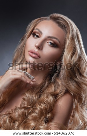 Beauty woman face with beautiful make-up colors. Blond hair, wavy hair, jewelry, clear skin, beautiful face. Portrait shot in studio on a gray background.